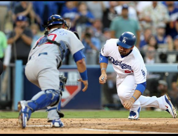Willson Contreras tags out Adrian Gonzalez at home plate in the second inning.  ROB LEITER/MLB PHOTOS