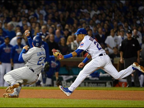 Addison Russell tags out Adrian Gonzalez in the sixth inning. RON VESELY/MLB PHOTOS